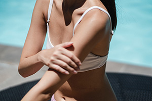 woman applying sunscreen by the pool